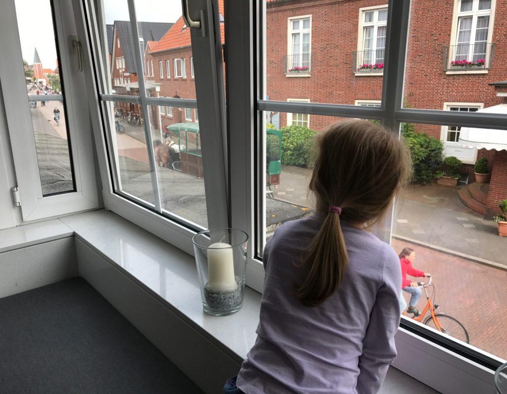 Urlaub auf Juist mit Kindern - Kind beobachtet Pferdekutsche durch das Fenster der Utlucht