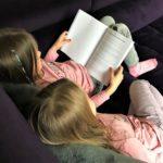 Geschwister beim Buch lesen